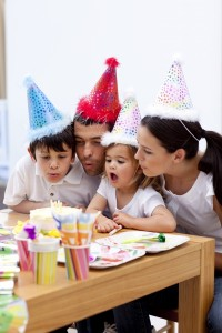 3678388-little-girl-blowing-out-candles-in-her-birthday-s-day-with-family